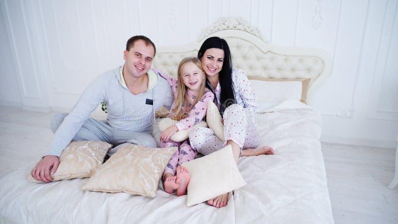 Genitori caucasici e piccola figlia che si siedono sul letto nella mattina, pigiami d'uso fotografia stock