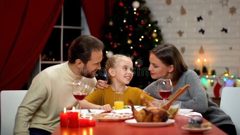Genitori che abbracciano figlia al pranzo di natale, famiglia felice che celebra vigilia di festa immagine stock libera da diritti