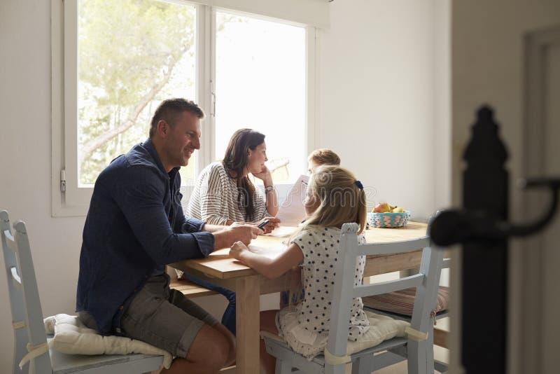 Genitori che aiutano i bambini con compito al tavolo da cucina fotografia stock