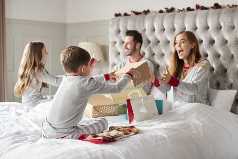 Genitori che aprono i regali dai bambini come essi Sit On Bed Exchanging Present sul giorno di Natale immagine stock libera da diritti