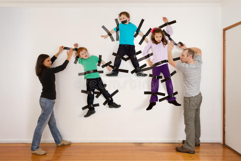 Genitori che attaccano i bambini allo scherzo della parete fotografia stock libera da diritti