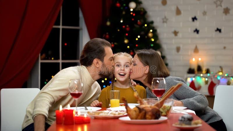 Genitori che baciano figlia sorridente alla cena di Natale, relazioni di famiglia immagine stock