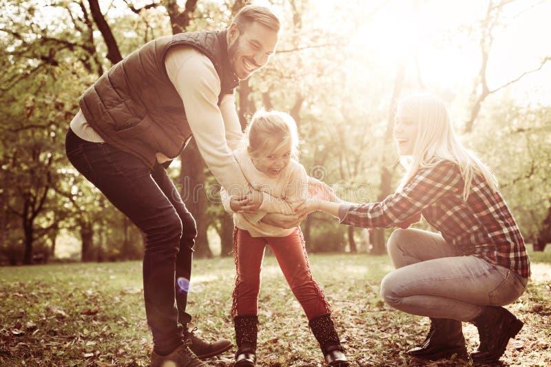 Genitori che giocano nel parco con la loro piccola figlia fotografie stock libere da diritti