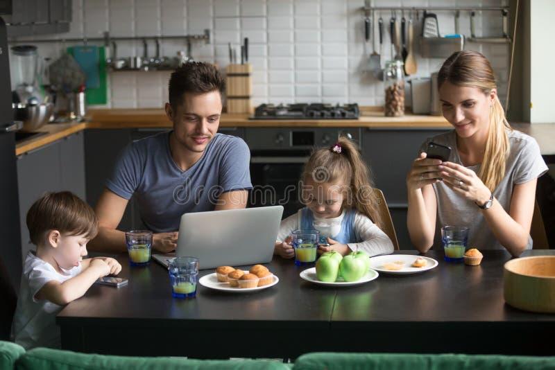 Genitori che per mezzo del computer portatile e degli smartphones che hanno wi della prima colazione di mattina fotografia stock libera da diritti
