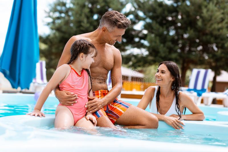 Genitori che ridono mentre nuotando nello stagno con la loro ragazza adorabile immagine stock libera da diritti