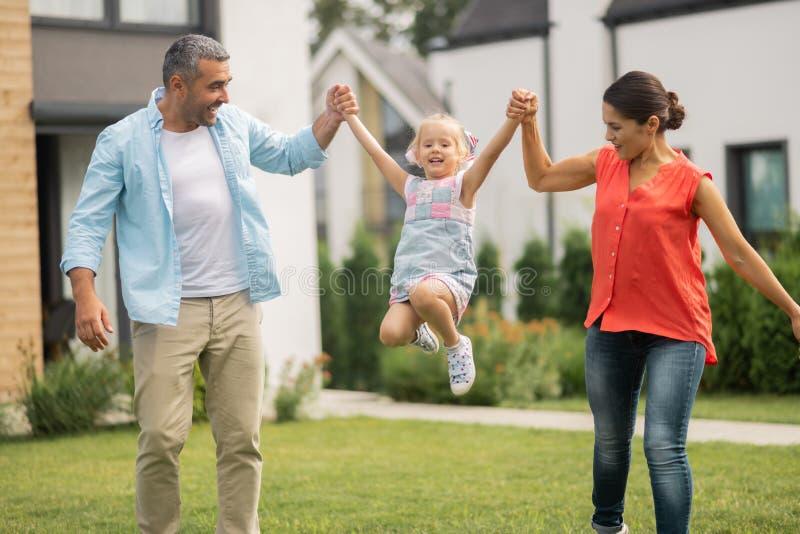 Genitori che sollevano la loro figlia divertente adorabile fuori della casa vicina immagine stock