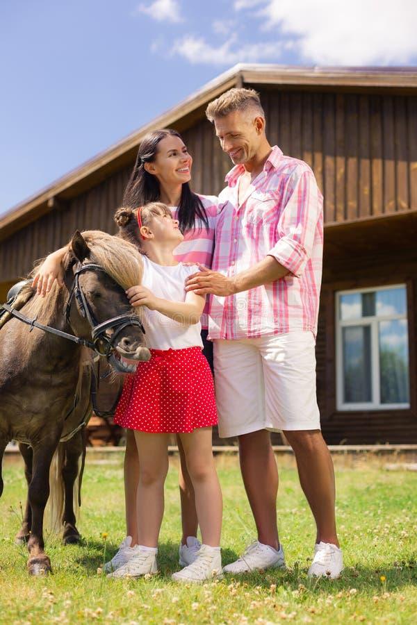 Genitori che stanno vicino alla figlia che tocca cavallo marrone piacevole fotografia stock