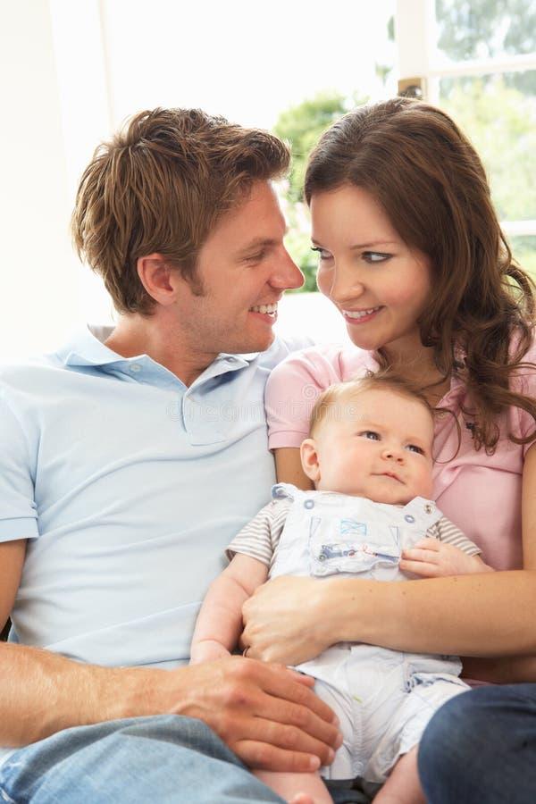 Genitori che stringono a sé neonato appena nato nel paese fotografie stock
