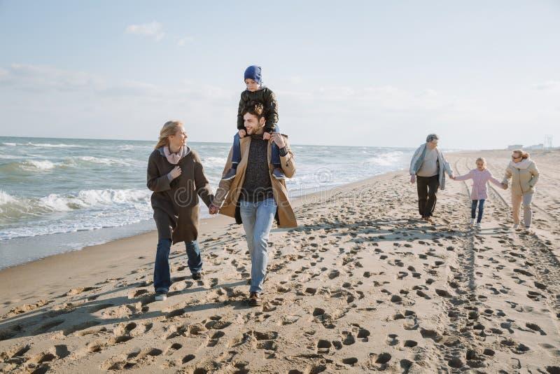 genitori che trasportano sulle spalle figlio mentre nonni che si tengono per mano con la nipote che cammina insieme immagini stock
