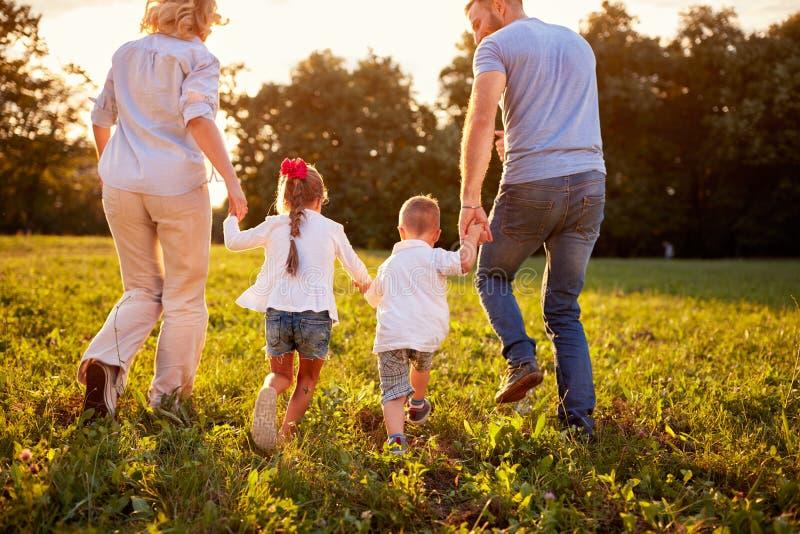 Genitori con i bambini che camminano in natura, vista posteriore fotografia stock libera da diritti