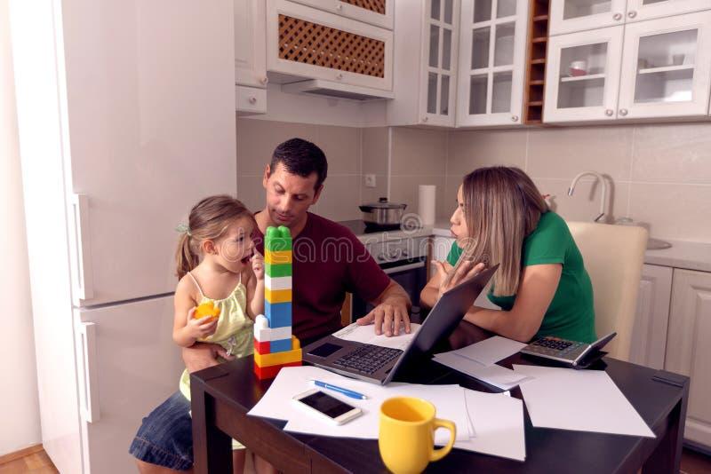 Genitori con la figlia che lavora dalla casa facendo uso del computer portatile fotografia stock libera da diritti