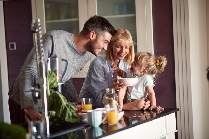 Genitori con la figlia divertendosi nella cucina immagini stock