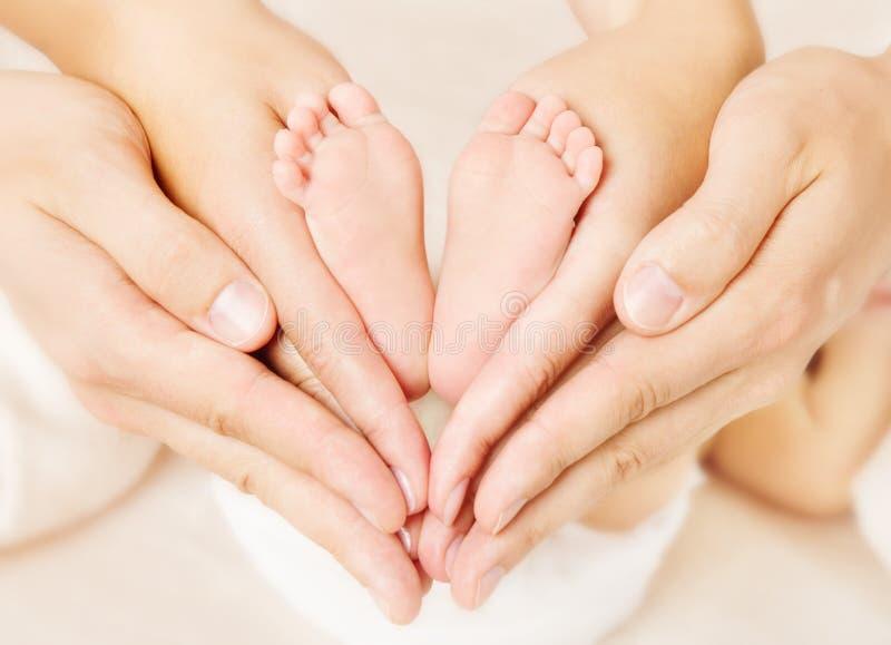 Genitori dei piedi del neonato che tengono in mani. fotografia stock