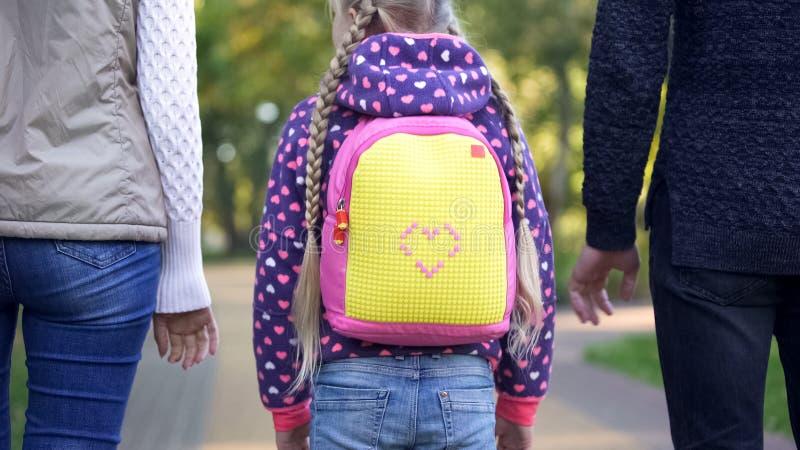 Genitori e figlia che vanno a scuola, paternità cosciente, cura, vista posteriore fotografia stock libera da diritti