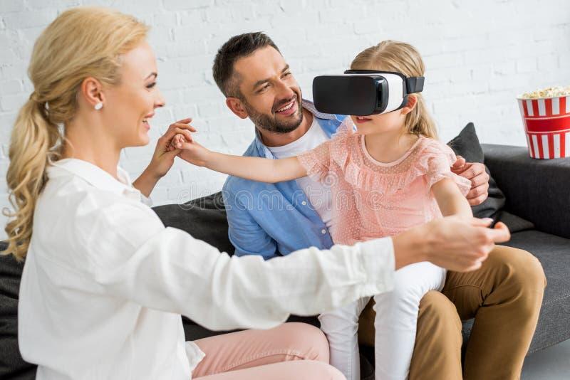 genitori felici che esaminano piccola figlia sveglia che per mezzo della cuffia avricolare di realtà virtuale fotografia stock