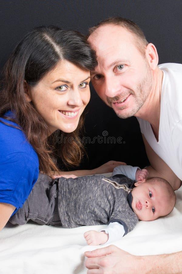 Genitori felici che giocano con il neonato adorabile immagine stock