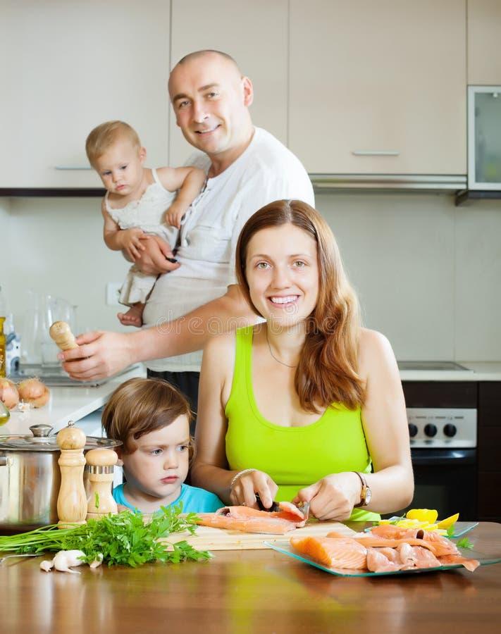 Genitori felici con i bambini che cucinano pesce immagine stock