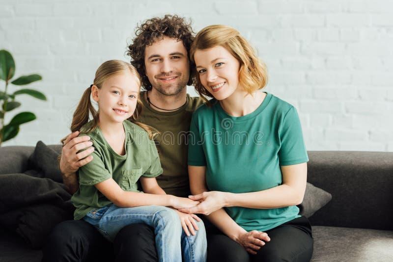 genitori felici con la piccola figlia sveglia che si siede sullo strato e sul sorridere fotografia stock libera da diritti