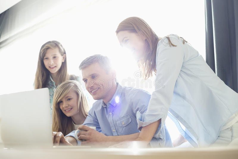 Genitori felici con le figlie che per mezzo del computer portatile a casa fotografia stock libera da diritti