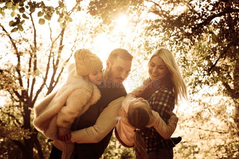 Genitori felici con le figlie in parco Fine in su fotografia stock