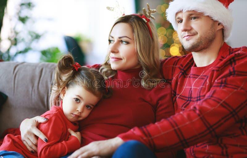Genitori felici della famiglia e presente aperti della figlia del bambino sulla mattina di natale immagini stock libere da diritti