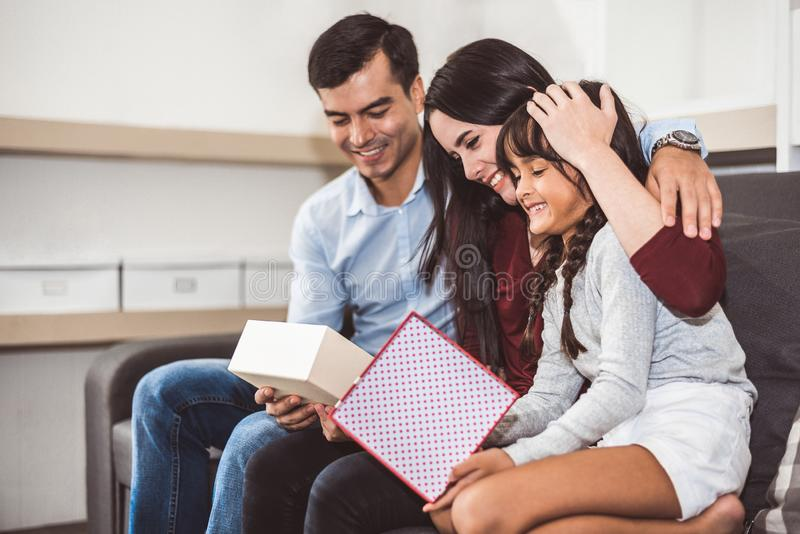 Genitori felici e bambina della famiglia che esaminano il contenitore di regalo nel Natale e nel capodanno sul sofà in salone Nat immagine stock
