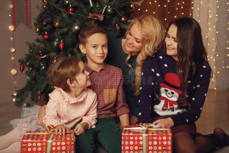 Genitori felici e bambini che dividono gli abbracci di Natale e che se esaminano fotografie stock