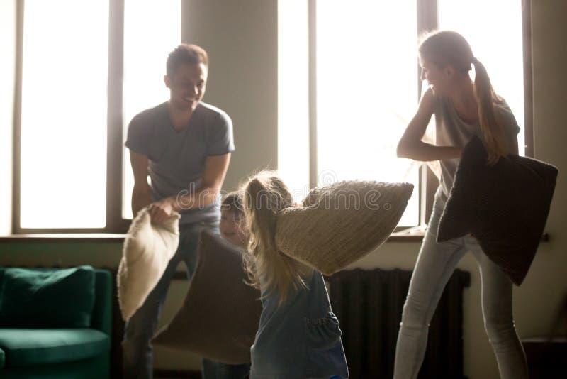 Genitori felici e bambini che ridono divertendosi lotta di cuscino all'interno immagine stock