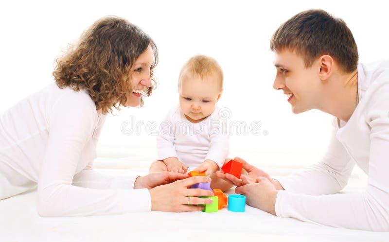 Genitori felici e bambino della famiglia che giocano con i giocattoli fotografia stock