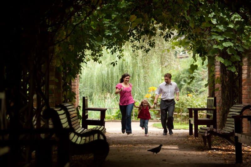 Genitori insieme alla figlia fatta funzionare sul traforo fotografia stock