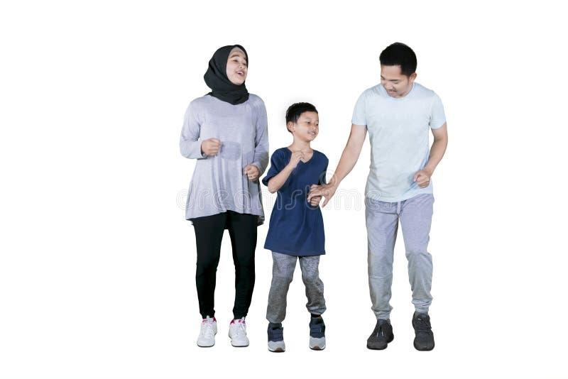 Genitori musulmani che fanno funzionamento di esercizio con il loro figlio fotografia stock libera da diritti