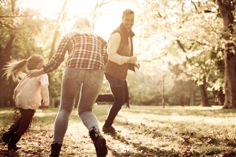 Genitori in parco che maneggia con la bambina e che gode in Au immagine stock