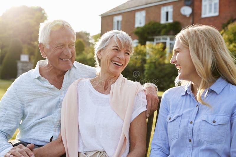 Genitori senior che si siedono su Seat in giardino con la figlia adulta fotografia stock