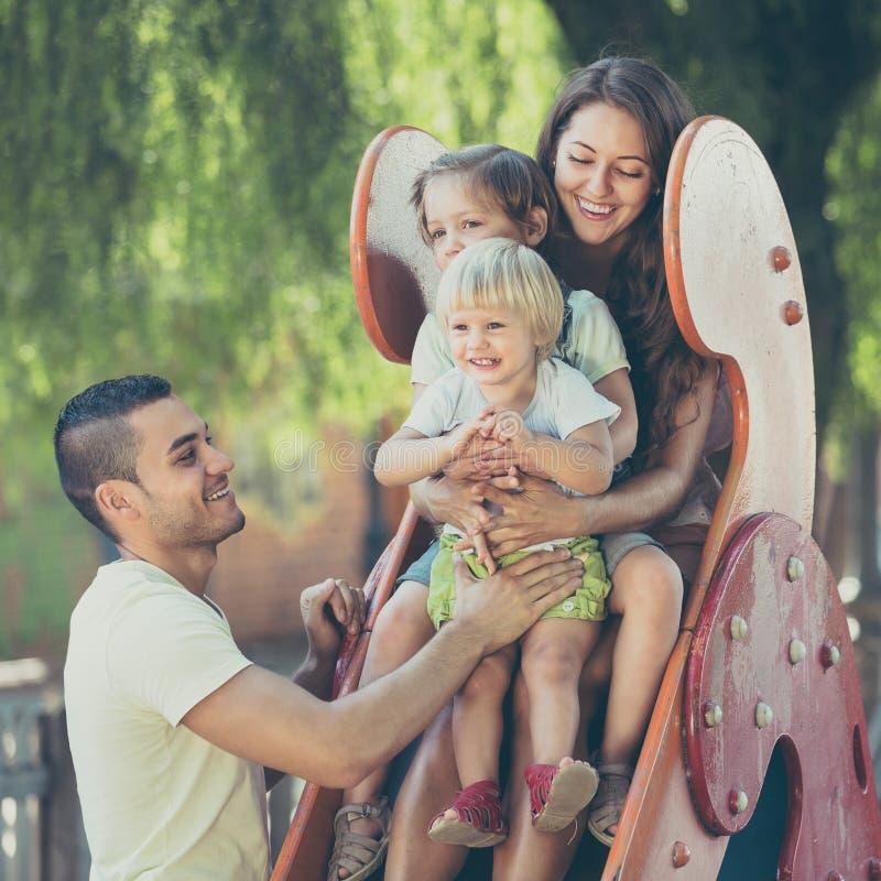 Genitori sorridenti che aiutano i bambini sullo scorrevole immagine stock