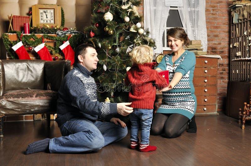 Genitori sorridenti che danno regalo di Natale al figlio a casa immagini stock