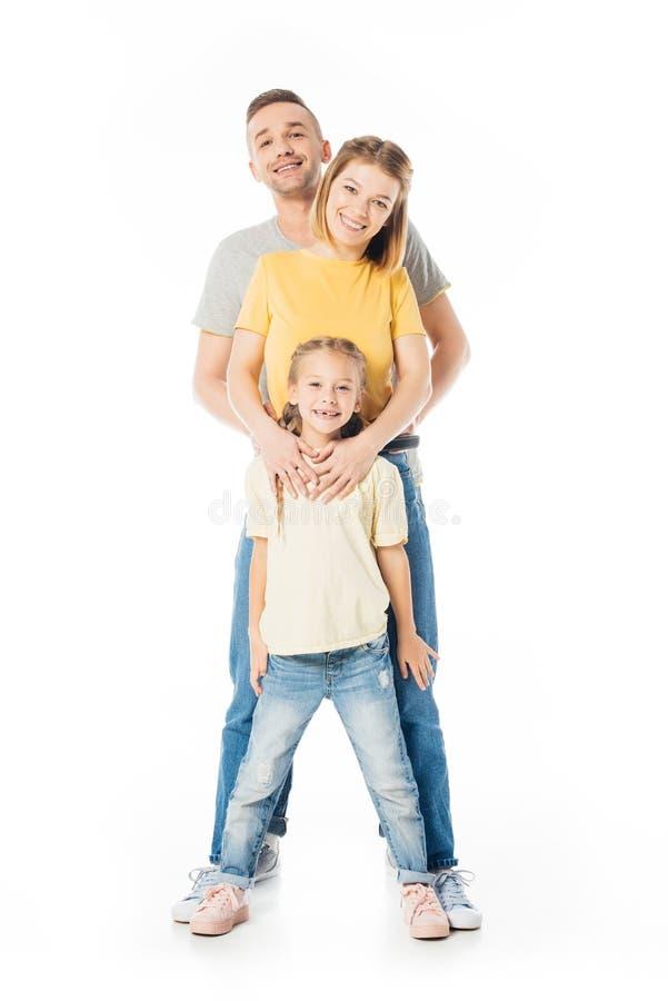 genitori sorridenti e piccola figlia che si abbracciano ed esame della macchina fotografica immagine stock libera da diritti