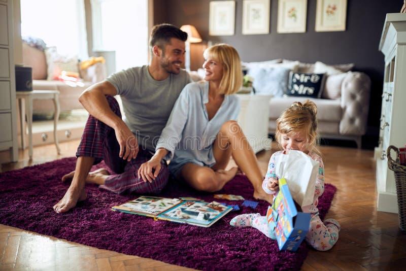 Genitori sorridenti nell'amore con la figlia in salone fotografia stock