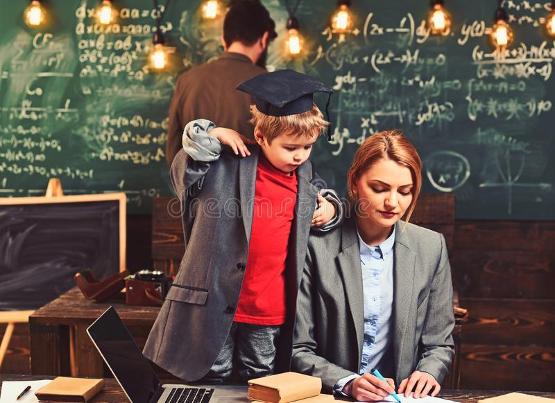 Genius boy teach woman and man at chalkboard. Son with mother and father have lesson. Little child and family in. Genius boy teach women and men at chalkboard royalty free stock photo