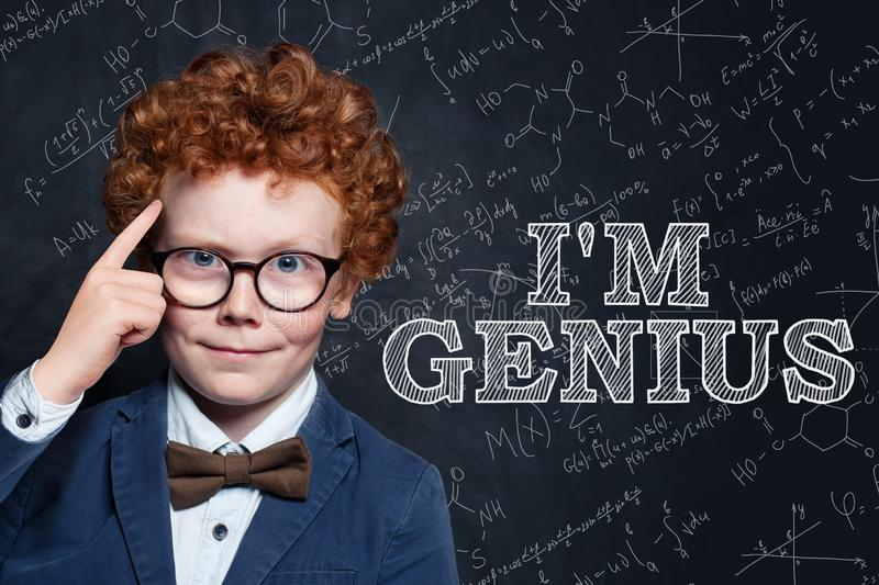 Genius child on blackboard background with science and maths formulas.  stock images