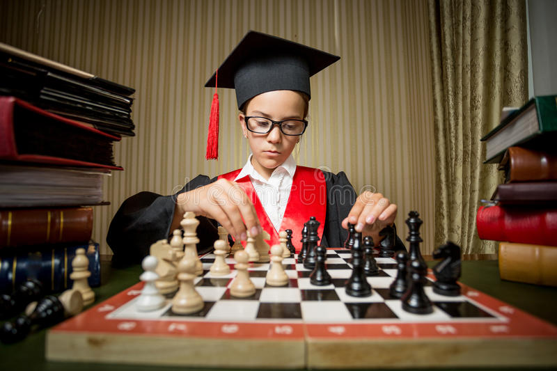 Genius girl in graduation cap playing chess with herself. Portrait of genius girl in graduation cap playing chess with herself royalty free stock images