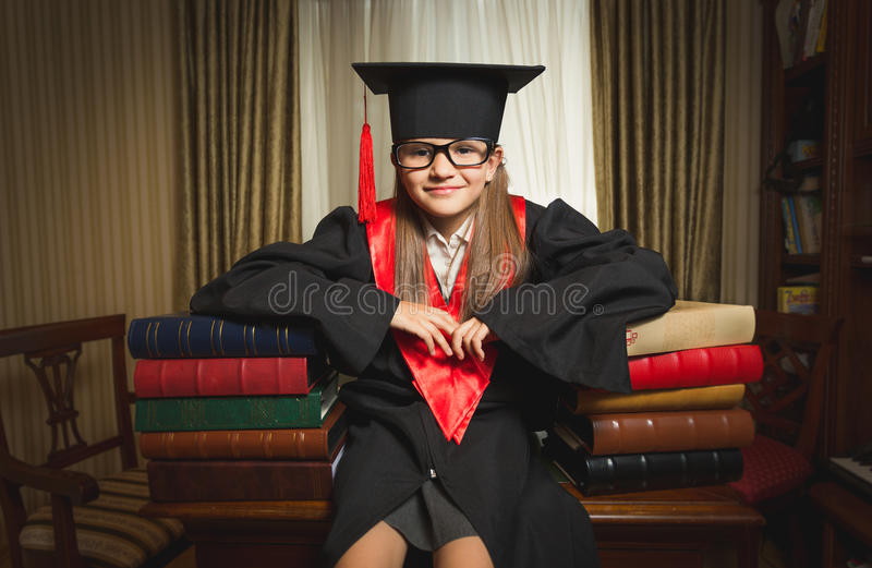 Genius girl in graduation clothes leaning on books at library. Portrait of little genius girl in graduation clothes leaning on books at library royalty free stock photography