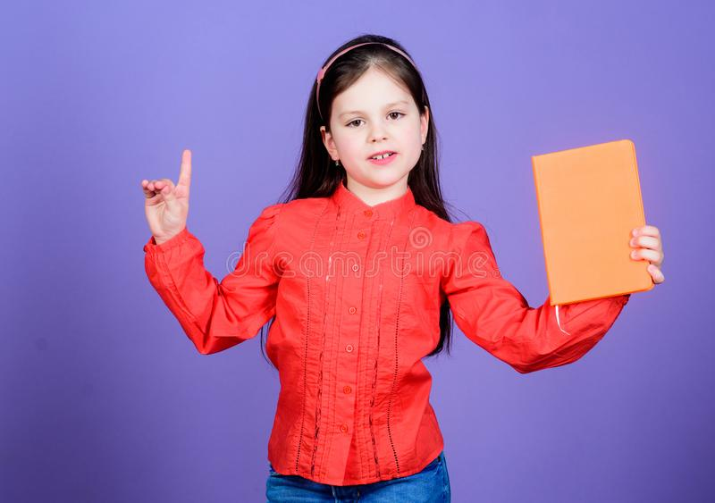 A genius idea. Adorable little child holding idea book and keeping finger raised. Cute small girl getting idea from book royalty free stock photo