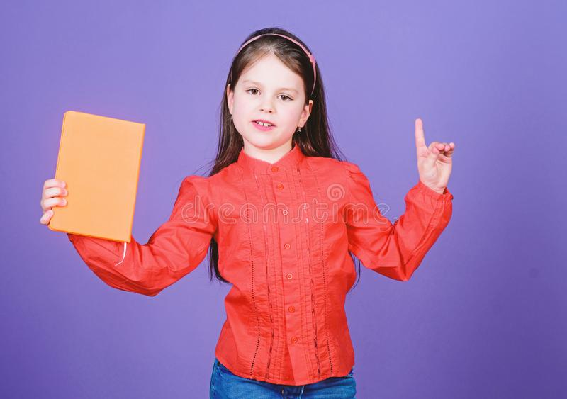 A genius idea. Adorable little child holding idea book and keeping finger raised. Cute small girl getting idea from book royalty free stock photography