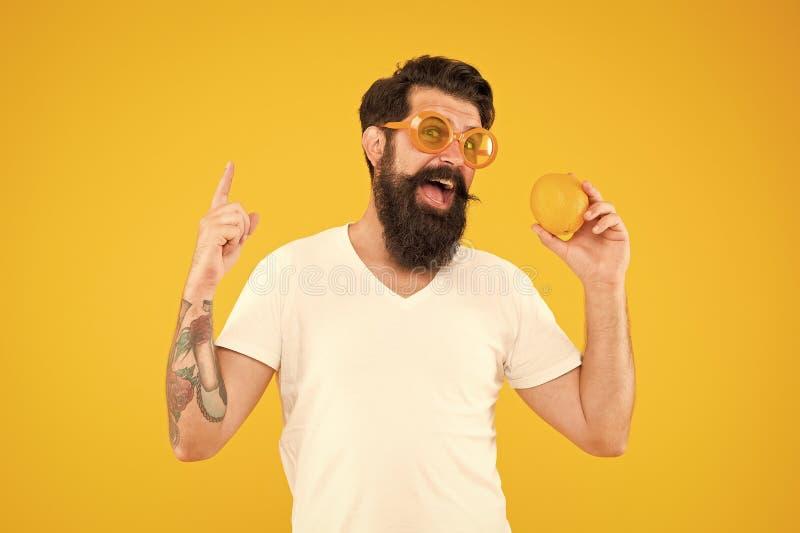 Genius orange inspiration. Genius man with orange pointing finger up on yellow background. Bearded hipster got genius stock image