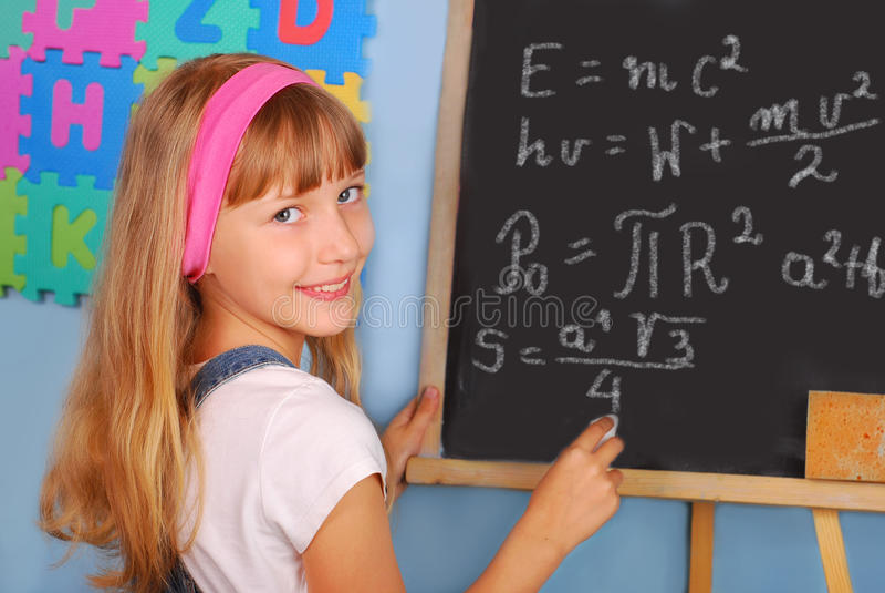 Genius schoolgirl writing on blackboard royalty free stock photos