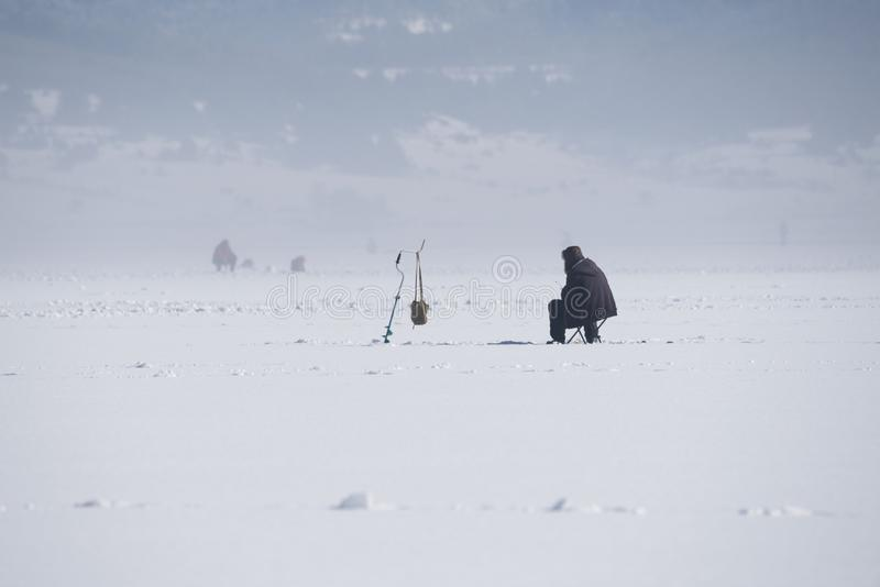 27 gennaio 2019, diga di poliana di Shiroka, Bulgaria Pesca sul ghiaccio su un lago congelato Coclea del ghiaccio e un uomo immagine stock libera da diritti