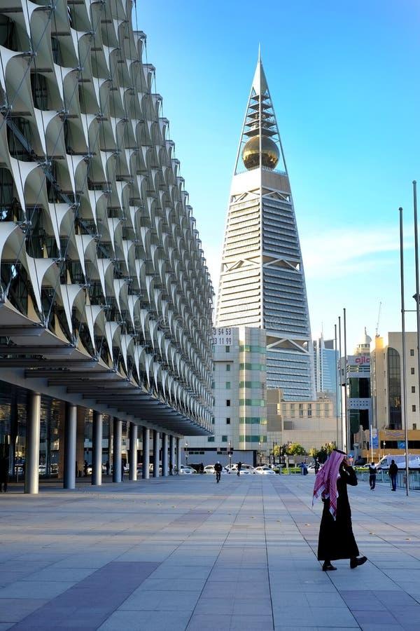 25 gennaio 2017 - Riyad, Arabia Saudita: Un uomo cammina vicino il parco e Al Faisaliyah Center Tower saudita del museo nazionale immagine stock libera da diritti
