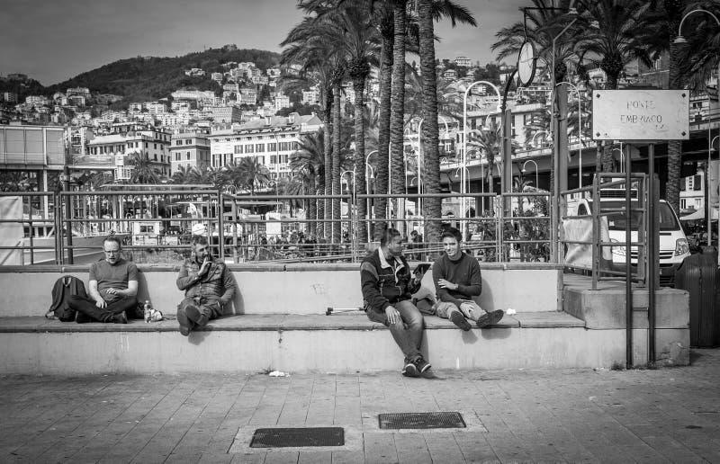 Genoa, Italy - April 21, 2016: People sitting on the main Genoa embankment benches in Genoa, Italy royalty free stock photography