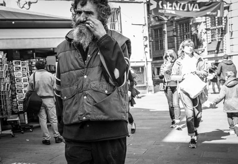 Genoa, Italy - April 21, 2016: Poor beggar walkink by the italian street in Genoa, Italy royalty free stock photos