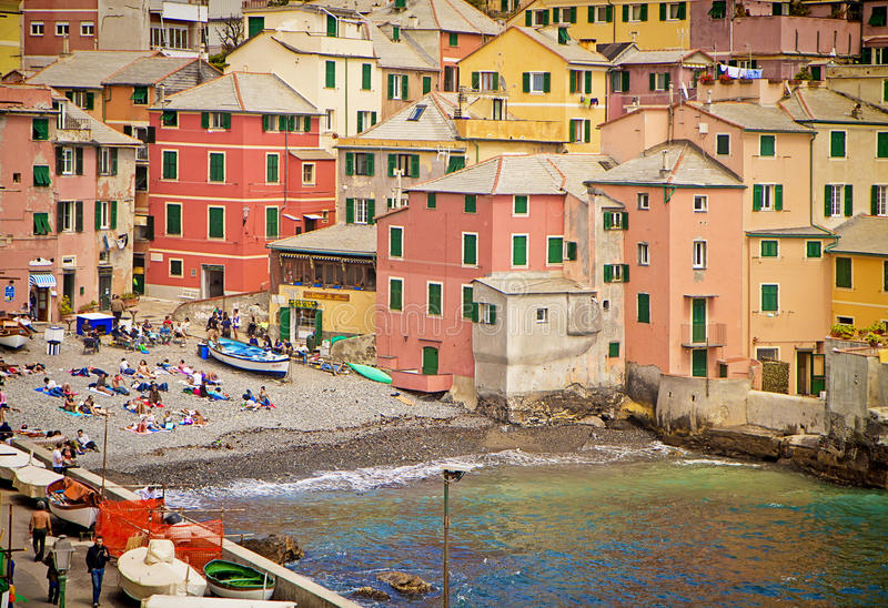 Genoa, Italy - bathers on the small shore of the Boccadasse bay. Genoa, Italy - Boccadasse bay shore with sun bathers. Boccadasse is a Genoa quarter and looks stock photo